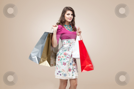 Studio portrait of a young woman in colourful outfit holding a f stock photo, studio portrait of a beautiful young woman, in a colourful outfit, holding in her hands a few shopping bags. she is laughing and looking very happy. by dan comaniciu