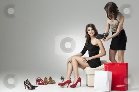 Two glamorous women trying high heels  stock photo, two glamorous women shopping high heels by dan comaniciu