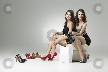 Two women trying high heels  stock photo, two glamorous women shopping high heels by dan comaniciu