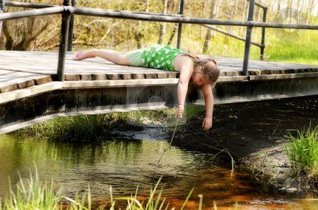 Girl Playing On Bridge stock photo, A young girl is leaning over a small bridge playing in the creek with a stick. by Richard Nelson