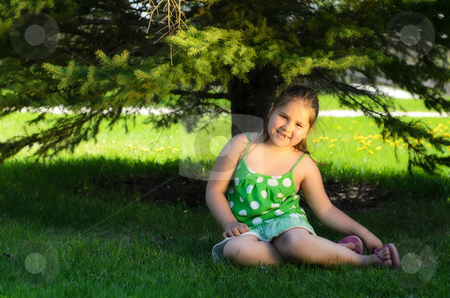 Young Girl Outside stock photo, A young girl sitting in the shade of a tree is smiling. by Richard Nelson