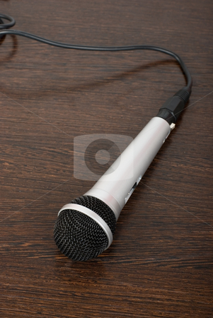Microphone stock photo, The microphone on a brown wooden background by olinchuk