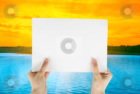 White paper stock photo, Hand holding white paper at beauty sunset on river background by olinchuk