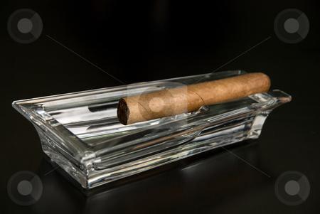 Cigar at ashtray stock photo, Cigar at ashtray isolated on a black back by olinchuk