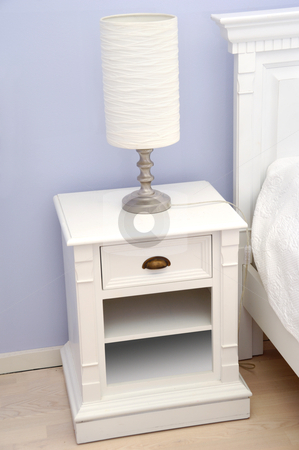 Bedside table with lamp stock photo, A white bedside table with a white lamp by Lars Christensen