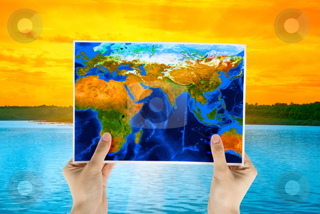 Map stock photo, Hand holding map at beauty sunset on Lake, and orange sky by olinchuk