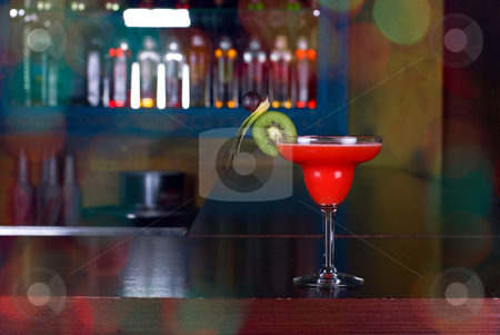 Red cocktail stock photo, red cocktail with kiwi on the wooden bar by olinchuk