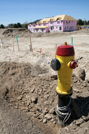 New Subdivision stock photo, A fire hydrant exposed from the ground in a new subdivision with a townhouse in the background.  by Chris Hill