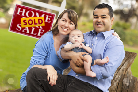 Mixed Race Couple, Baby, Sold Real Estate Sign stock photo, Happy Mixed Race Couple with Baby in Front of Sold Real Estate Sign. by Andy Dean