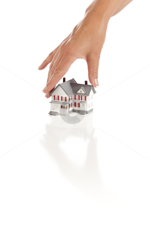 Womans Hand Choosing A Home on White stock photo, Womans Hand Choosing A Home on a White Background. by Andy Dean