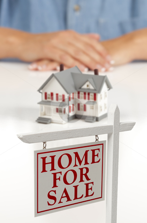 Womans Hands Behind House and Real Estate Sign in Front stock photo, Womans Folded Hands Behind Model House and Home For Sale Real Estate Sign In Front on White Surface. by Andy Dean