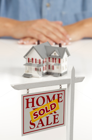 Womans Hands Behind House and Sold Real Estate Sign stock photo, Womans Folded Hands Behind Model House and Sold Home For Sale Real Estate Sign In Front on White Surface. by Andy Dean