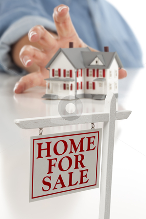 Real Estate Sign in Front of Woman Reaching for House stock photo, Real Estate Sign in Front of Womans Hand Reaching for Model House on a White Surface. by Andy Dean