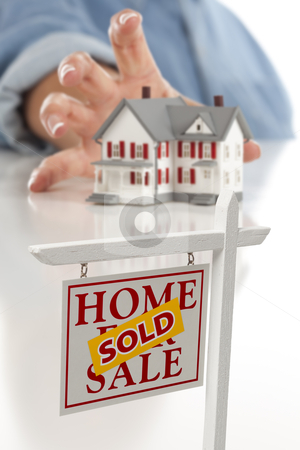 Sold Real Estate Sign in Front, Woman Reaching for House stock photo, Sold Real Estate Sign in Front of Womans Hand Reaching for Model House on a White Surface. by Andy Dean