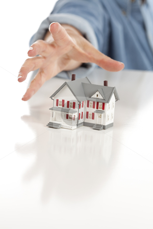 Womans Hand Reaching for Model House on White stock photo, Womans Hand Reaching for Model House on a White Surface. by Andy Dean