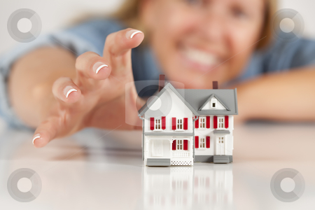 Smiling Woman Reaching for Model House on White stock photo, Smiling Woman Reaching for Model House on a White Surface. by Andy Dean