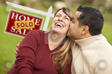 Mixed Race Couple in Front of Sold Real Estate Sign stock photo, Happy Mixed Race Couple in Front of Sold Real Estate Sign. by Andy Dean