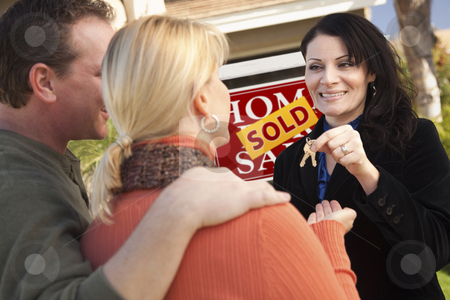 Attractive Hispanic Female Real Estate Agent Handing Over Keys stock photo, Attractive Hispanic Female Real Estate Agent Handing Over New House Keys to Happy Couple. by Andy Dean