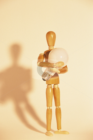 Wooden Mannequin Holding Light Bulb stock photo, Artists mannequin holding a lightbulb, concept photography by Bryan Mullennix