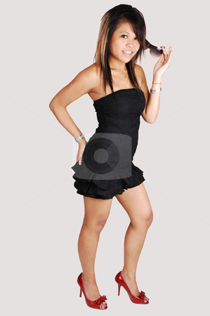 Asian girl in black dress. stock photo, A young Asian woman standing in red high heels and a short black dress in the studio, playing with her hair, holding her butt, on light gray background.  by Horst Petzold