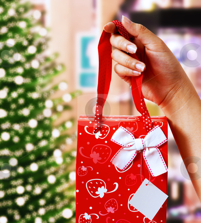 Holding Up A Christmas Gift stock photo, Holding Up A Christmas Gift In Front Of A Xmas Tree With Lights  by stuartmiles