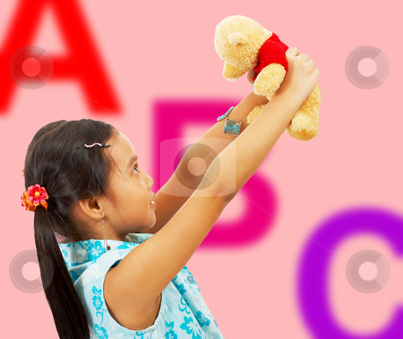Girl Holding Her Teddy Bear Up In The Air stock photo, Girl Holding Her Teddy Bear Up In The Air - In Her Playroom With ABC Background by stuartmiles