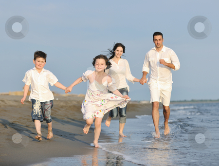 Happy young family have fun on beach at sunset stock photo, happy young family have fun on beach run and jump  at sunset by Benis Arapovic