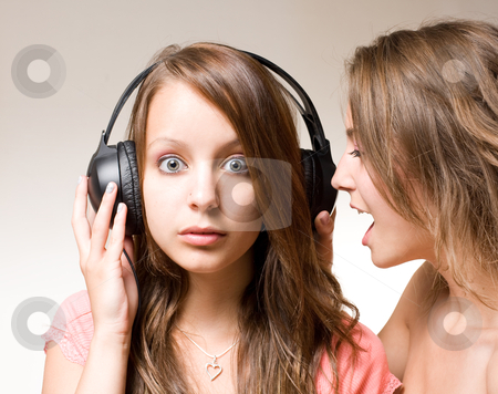Share the music!! stock photo, Share the music, two gorgeous brunette girls one shouting into other's ear with headhones lifted. by exvivo