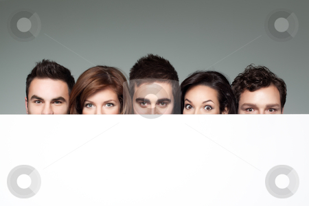 Funny faces behind white board stock photo, big eyes showing beside copy space for advertising by dan comaniciu