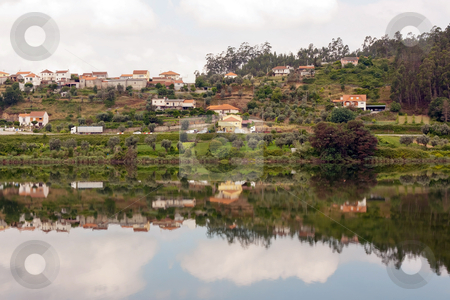 Landscape of a small village with its reflection in the river stock photo, Landscape of a small village with its reflection in the river by Paulo M.F. Pires