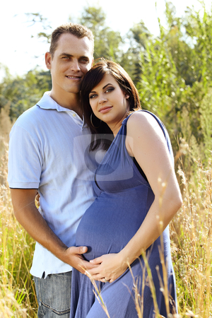 Man and pregnant wife in field stock photo, man and his pregnant wife in blue dress utdoors in field with long grass holding hands on stomach by lubavnel