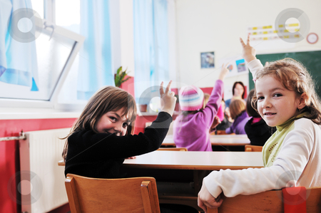 Happy kids with  teacher in  school classroom stock photo, happy young teacher woman at elementrary school teaching and giving leassons to group of young smart children by Benis Arapovic
