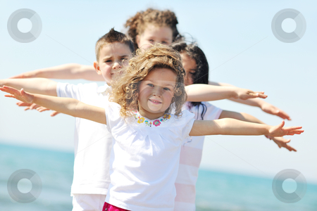 Happy child group playing  on beach stock photo, group of happy child on beach who have fun and play games by Benis Arapovic