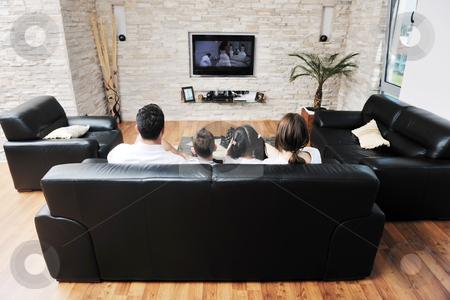 Family wathching flat tv at modern home indoor stock photo, happy young family wathching flat tv at modern home indoor by Benis Arapovic
