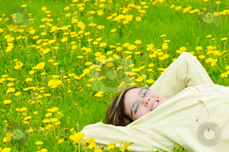Girl Relaxing In The Sun stock photo, A young preteen girl is lying in the grass, relaxing in the sun. by Richard Nelson