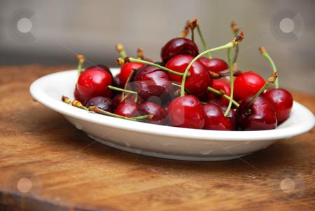 Appetizing fresh cherries stock photo, heap of fresh appetizing red cherries on plate indoors by Julija Sapic