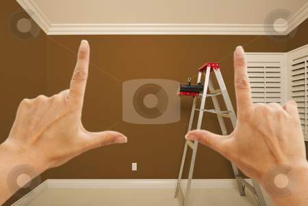 Hands Framing Brown Painted Wall Interior stock photo, Hands Framing Brown Painted Room Wall Interior with Ladder, Paint Bucket and Rollers. by Andy Dean