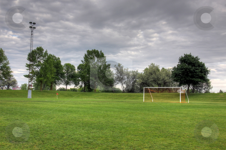 Cloudy Soccer Field stock photo, A cloudy unoccupied soccer field with trees in the background. (HDR photograph) by Chris Hill
