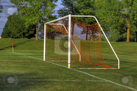 Soccer Goal Side-view stock photo, An empty soccer goal with trees in the background. (HDR photo)  by Chris Hill