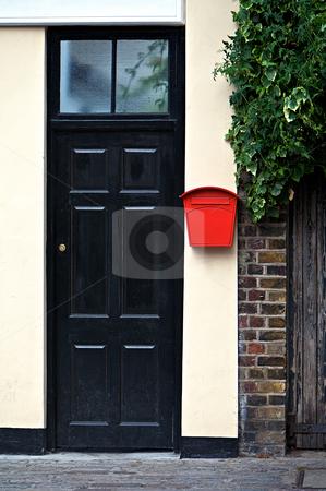 Door stock photo, Black door front with red letter box by Vividrange