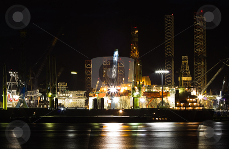 Shiprepair and dock at night stock photo, Shiprepair and dock at night - industrial, ships in foreground and drilling platforms in background by Colette Planken-Kooij