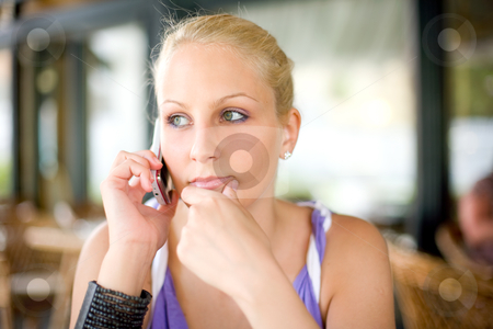 Gorgoeus young blonde talking on her mobile phone. stock photo, Gorgoeus young blonde talking on her mobile phone with thoughtful facial expression. by exvivo