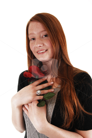 Girl with red rose. stock photo, A young woman with long red hair holding a red rose close to her chest and smiling into the camera, for white background.  by Horst Petzold