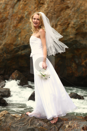 Pretty Blonde Bride Along the Ocean  stock photo, Beautiful Blonde Bride at the Beach on Her Wedding Day by Katrina Brown