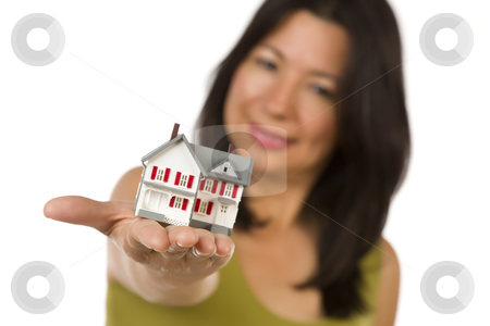 Attractive Multiethnic Woman Holding Small House stock photo, Attractive Multiethnic Woman Holding a Small House Out In Front of Her Isolated on a White Background. by Andy Dean