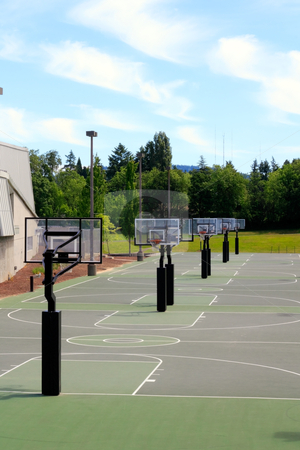 Game Day stock photo, Several green basketball courts outdoors with a landscape and sunny sky with some clouds on the first day of summer. by Lee Serenethos