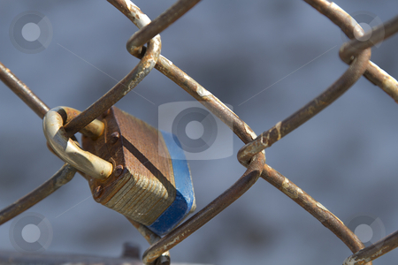 Padlock fence stock photo, Close up view of a rusted pad lock attach to a chain link fence by Yann Poirier