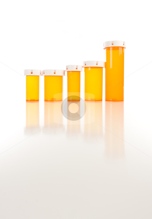 Empty Medicine Bottles on Reflective Surface stock photo, Several Different Sized Empty Medicine Bottles as Increasing Graph on Reflective Surface. by Andy Dean