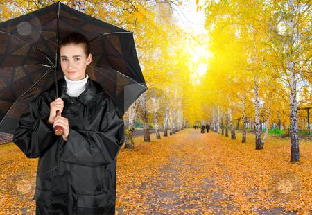 Umbrella stock photo, pretty brunette girl at black coat under umbrella by olinchuk