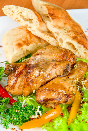 Roasted chicken drumstick stock photo, roasted chicken drumstick garnished with fresh green salad, pepper and greens by olinchuk